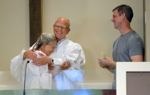 East Boulder Baptist Church Senior Pastor Larry Dramann (center) is embraced by Donna Gail following her baptism at the church. Gail's friend, Travis Kunckel (right), traveled from Texas with his family to attend the service. Kunckel and his wife, Denise, discipled Gail. NAMB photo by Susan Whitley