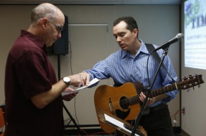Jeff Guillard, left, and Michael Johnson go over the schedule for Sunday worship before the River Church meeting in the Community Room in Moxee City Hall in Moxee, Wash. on Oct. 19, 2014. (KAITLYN BERNAUER)
