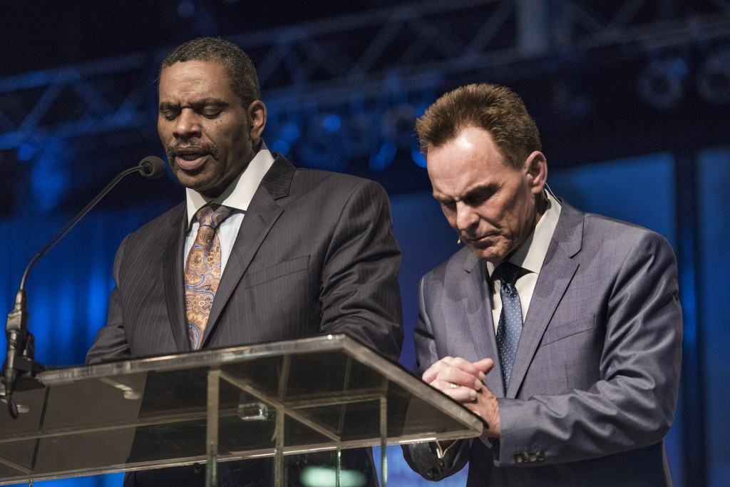 """K. Marshall Williams, left, senior pastor of Nazarene Baptist Church in Philadelphia, prays next to Ronnie Floyd, president of the Southern Baptist Convention, during the June 16 evening prayer session of the SBC annual meeting at the Greater Columbus Convention Center. """"It's time for us to be the people of God"""" and to love one another regardless of race or ethnicity, he prayed. Photo by Paul W. Lee"""