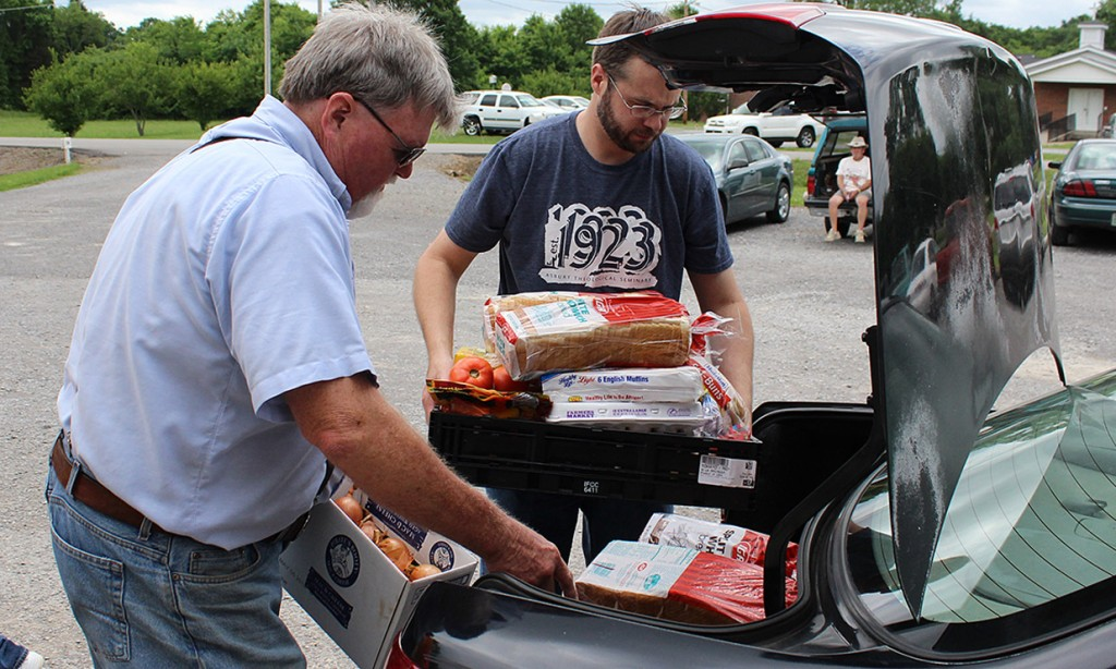 Doug Mitchell (left), pastor of Midland Baptist Church in rural Tennessee, and Roger Brown of Cedar Grove United Methodist Church, load food into the car of a family receiving aid at Midland's Journey of Hope Ministry Center. Photo by Lonnie Wilkey