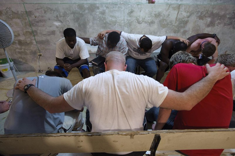 A missions-centered church prays together. Members of a student volunteer team from Middle Georgia College in Cochran, Ga., pray together during an evening devotional time in the basement of First Baptist Church of Carrefour, Haiti. IMB Photo